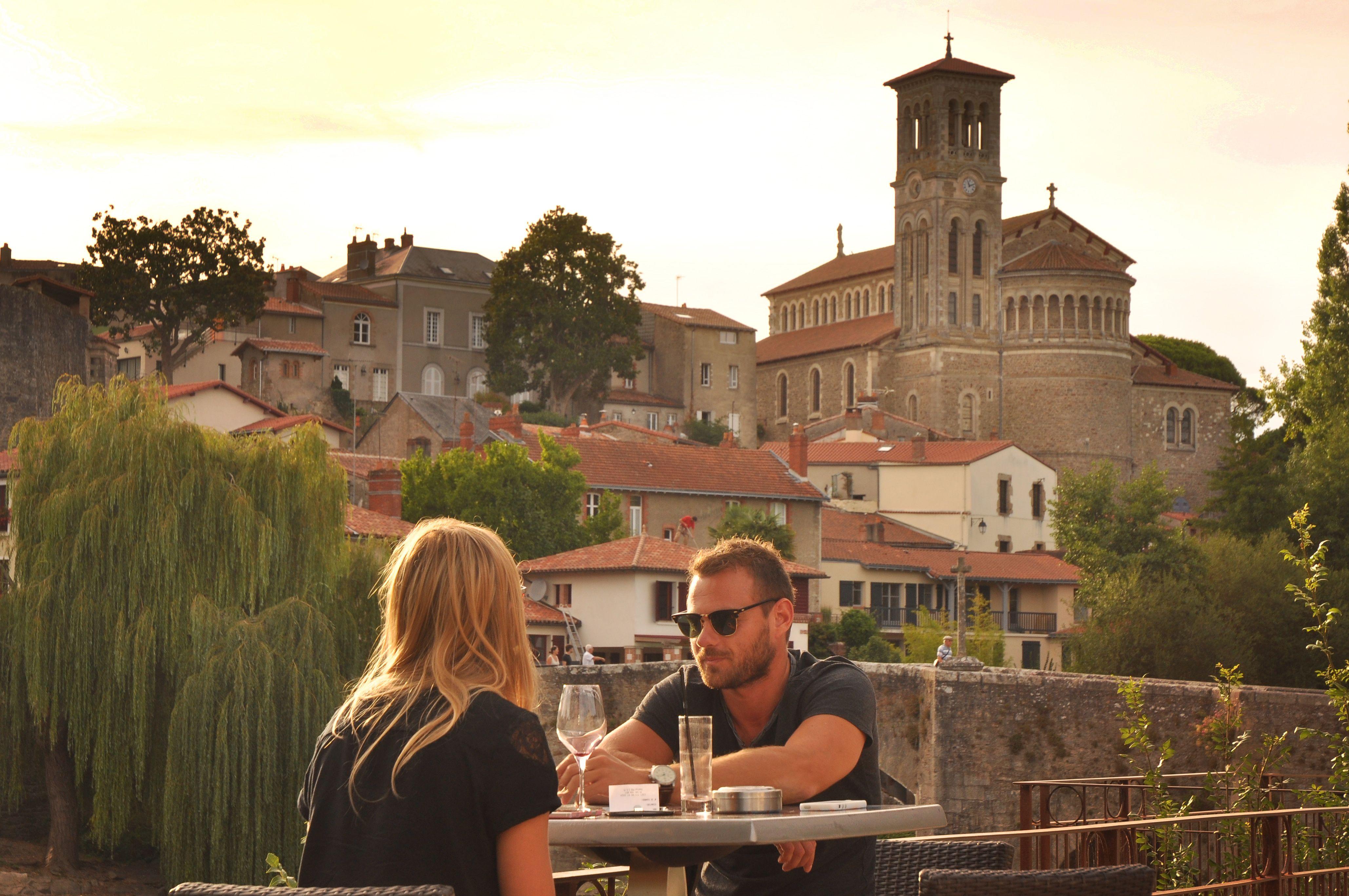 couple assis à une table de restaurant devant la cité médiévale de Clisson, en Loire-Atlantique