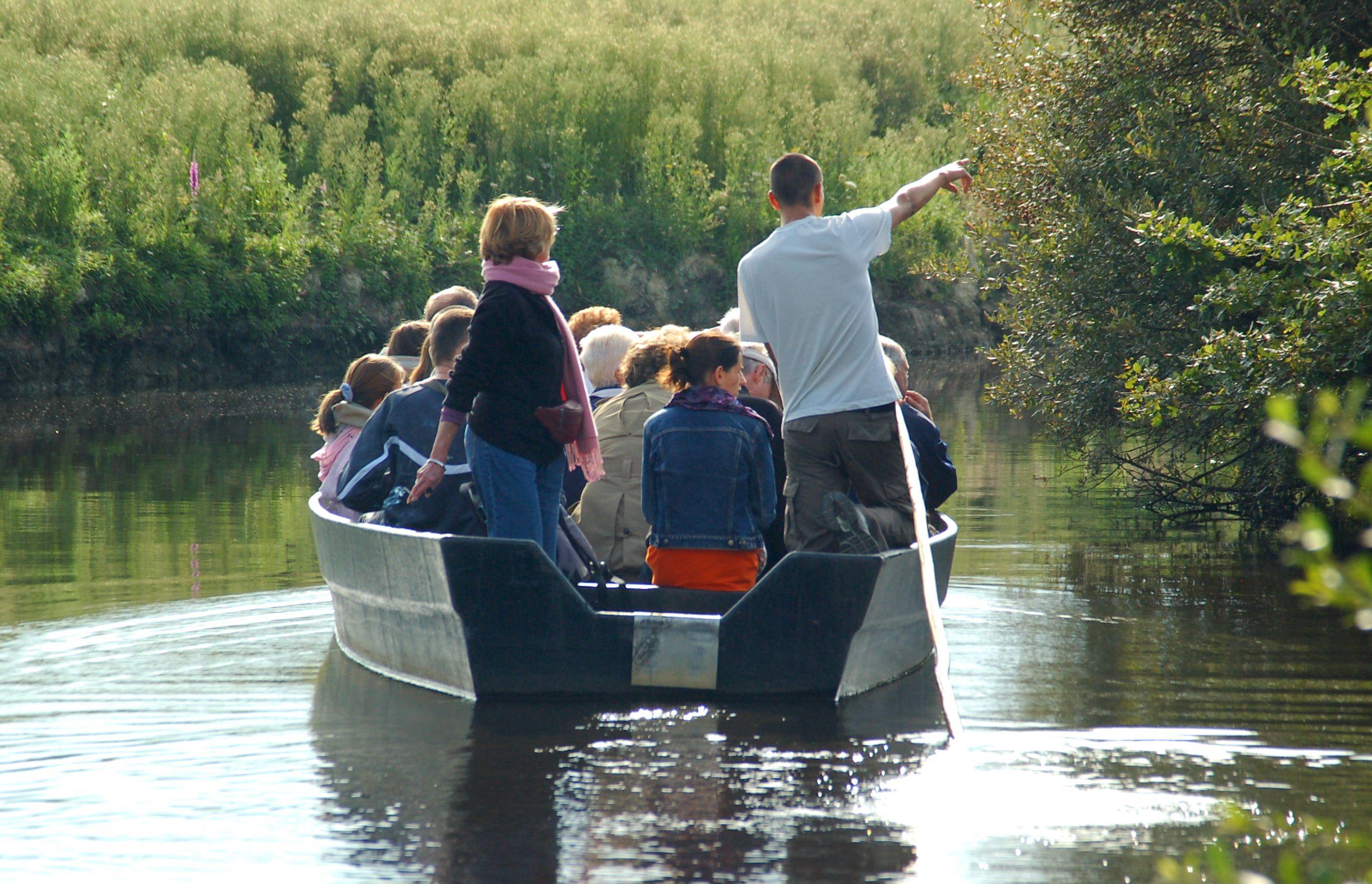 Touristes assis sur une barque avec un guide, en Loire-Atlantique