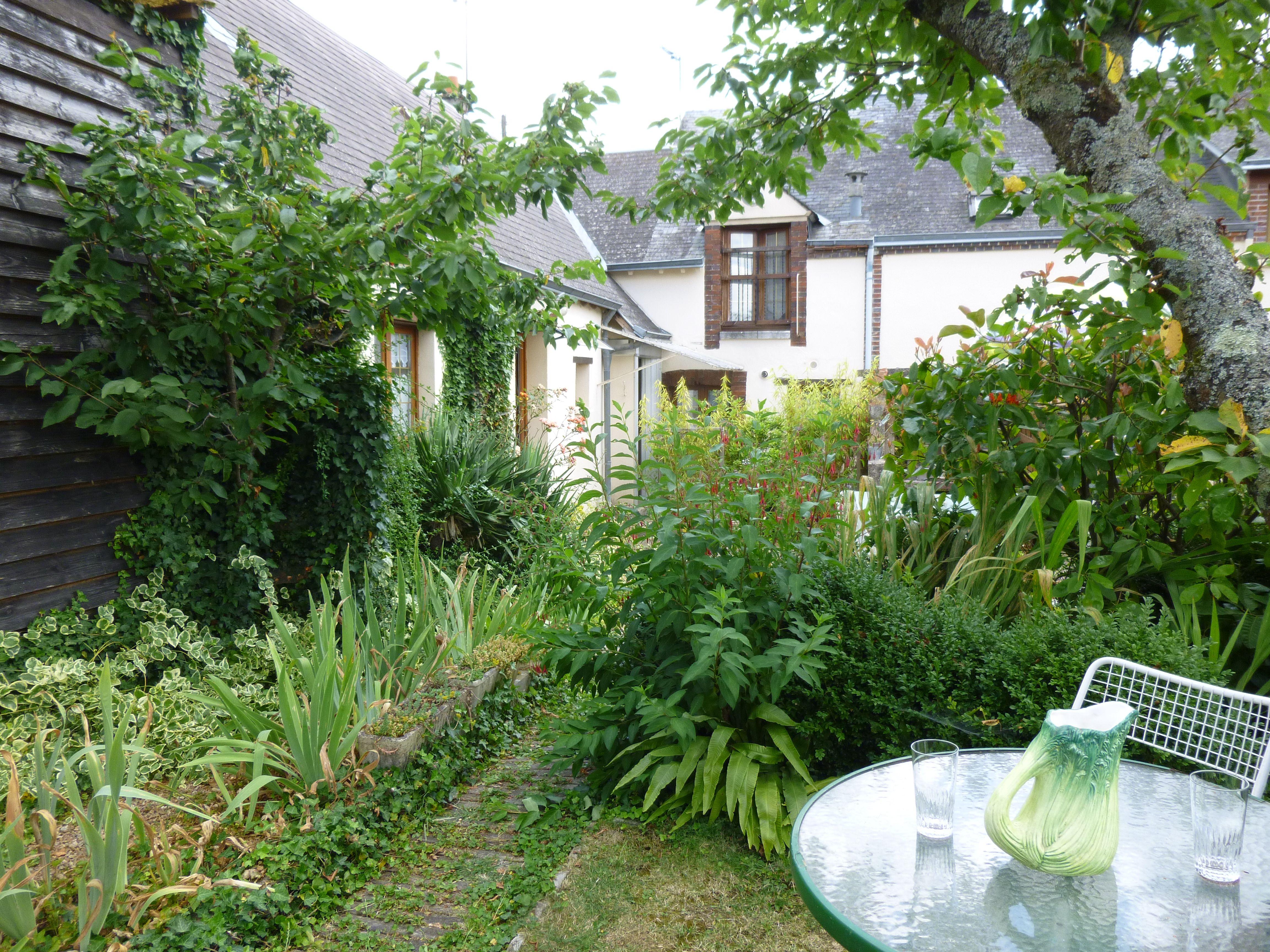 Un jardin fleuri avec terrasse, barbecue et local pêche