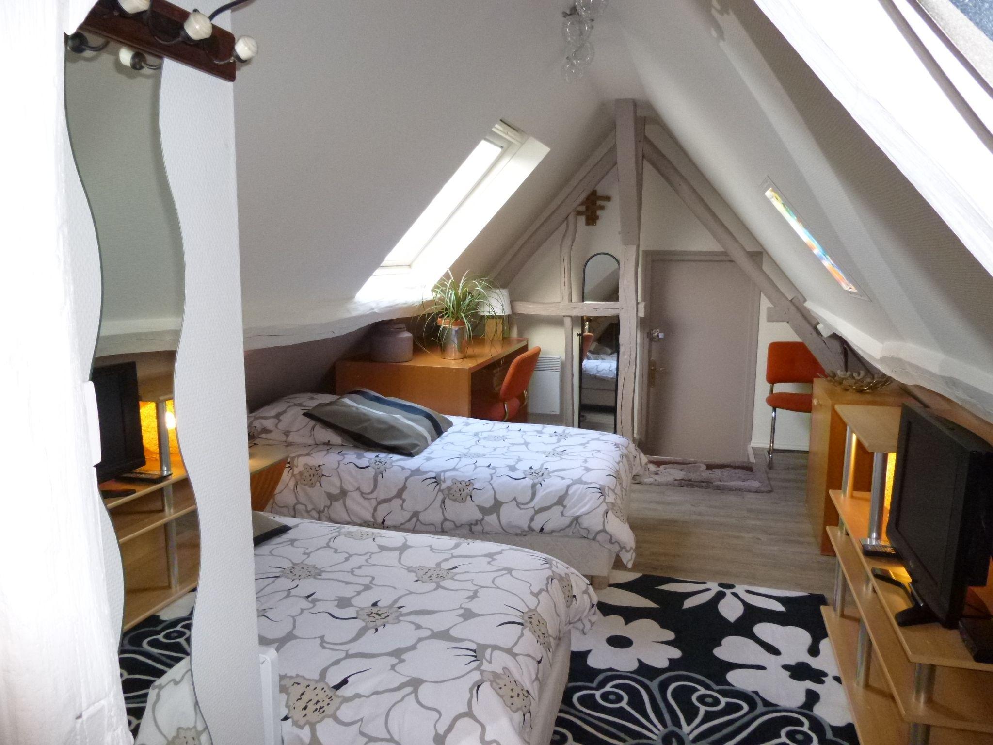Chambre et salle de bain avec baignoire, sous le toit