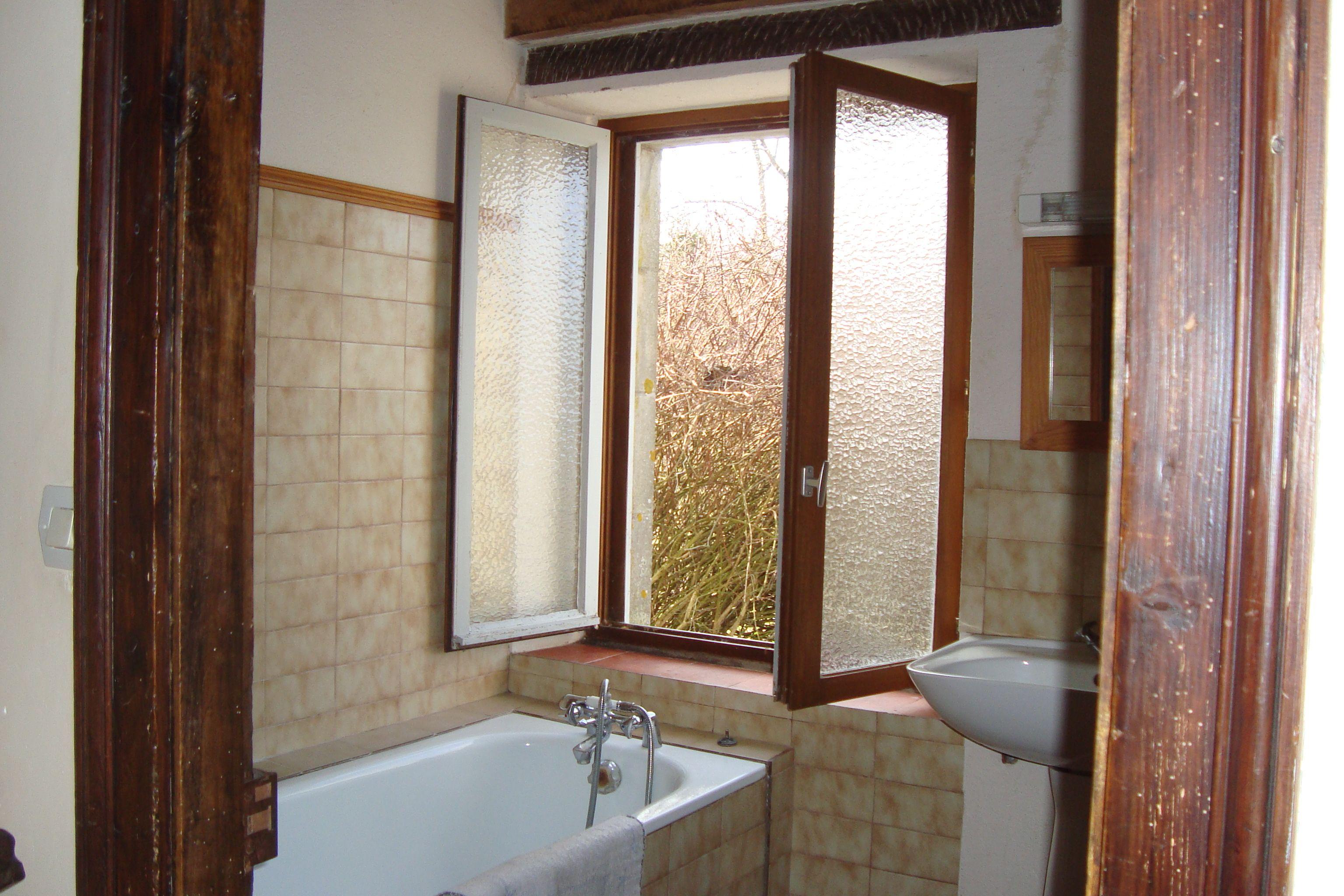 La salle de bains du rez-de-chaussée avec sèche serviettes, toilettes et sèche-linge