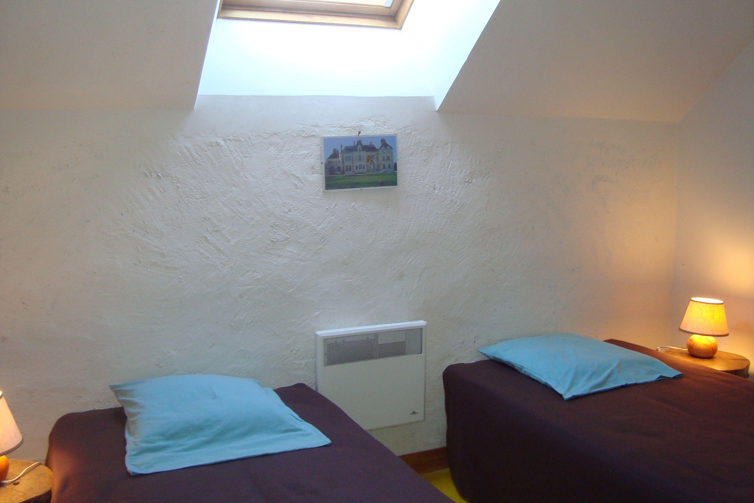Chambre Baptiste, 2 lits jumeaux, 2 tables de nuit, une étagère à 6 rayonnages, porte manteaux sur la porte