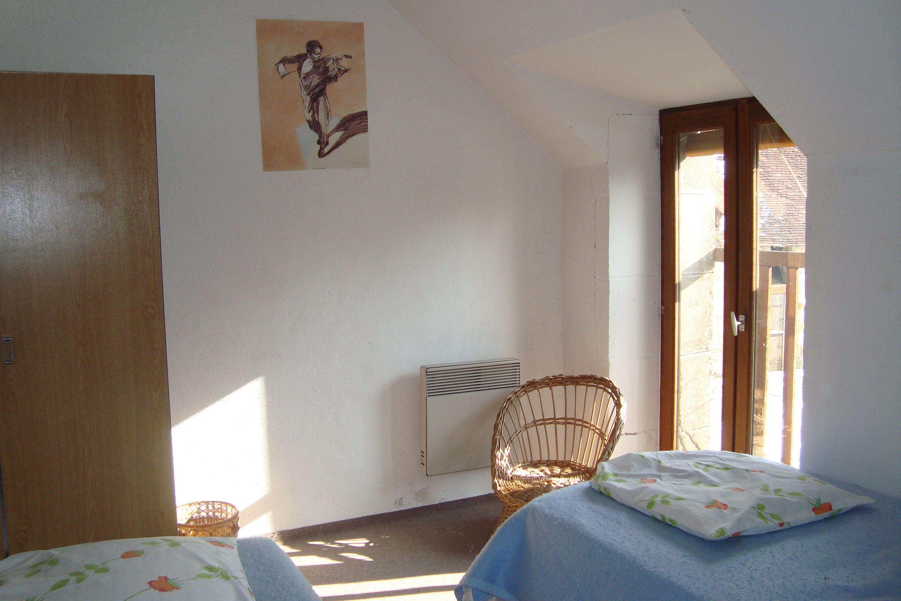 Chambre Colas, 2 lits jumeaux, porte-fenêtre balustrade donnant sur le jardin du gîte, une étagère encadrant les lits et une armoire