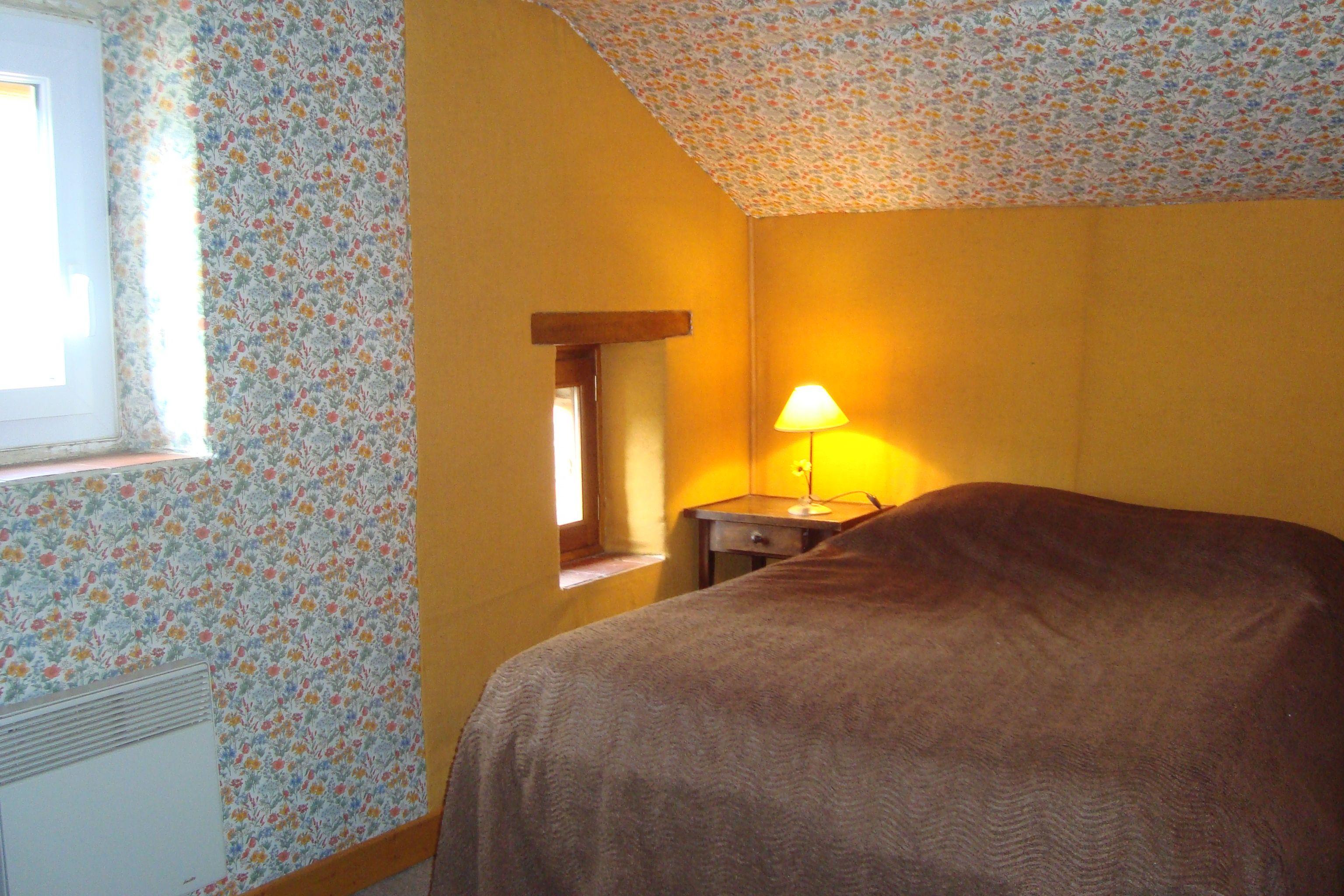 Chambre le Pigeonnier, un lit double, 2 petites fenêtres donnant sur la campagne, une penderie, une commode