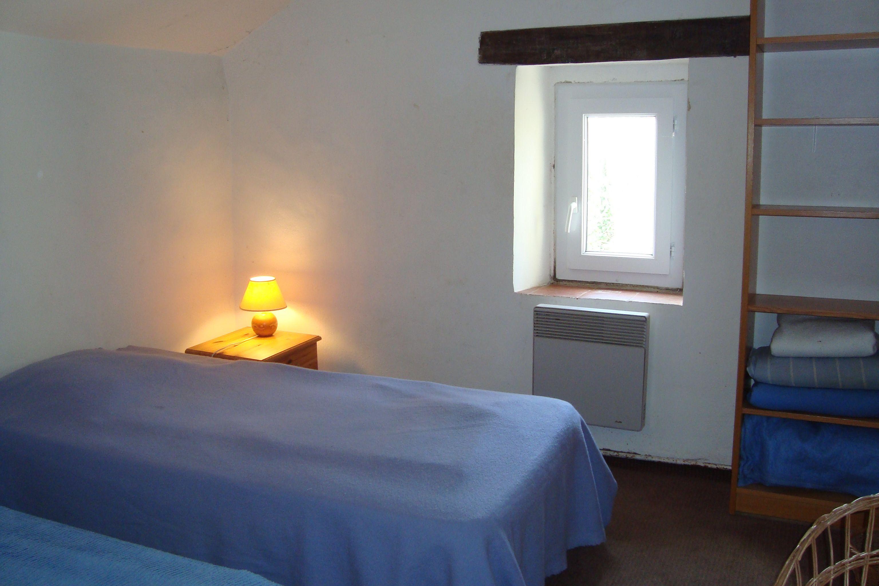 Chambre l'Etang, 2 lits jumeaux, une fenêtre donnant sur l'étang, 2 tables de nuit, une étagère à 6 rayonnages, porte-manteaux sur la porte