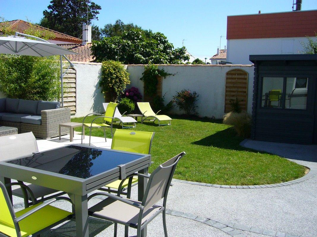Jardin clos de 100 m² équipé d'un salon, relaxes,table, chaises et plancha.