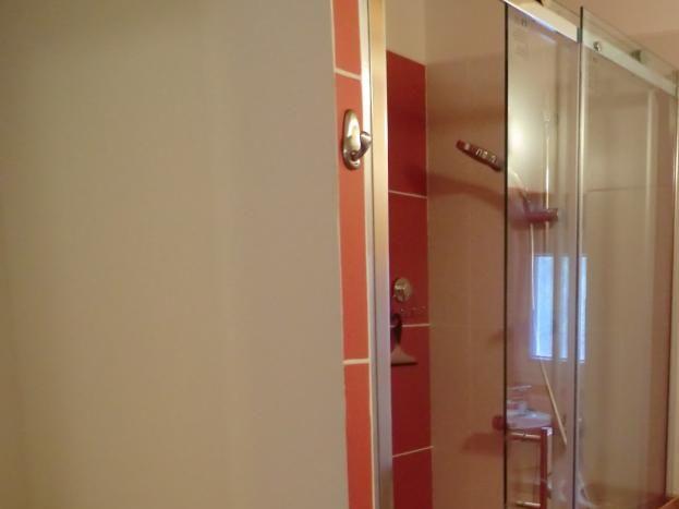 salle de bain avec une grande douche et meuble à langer