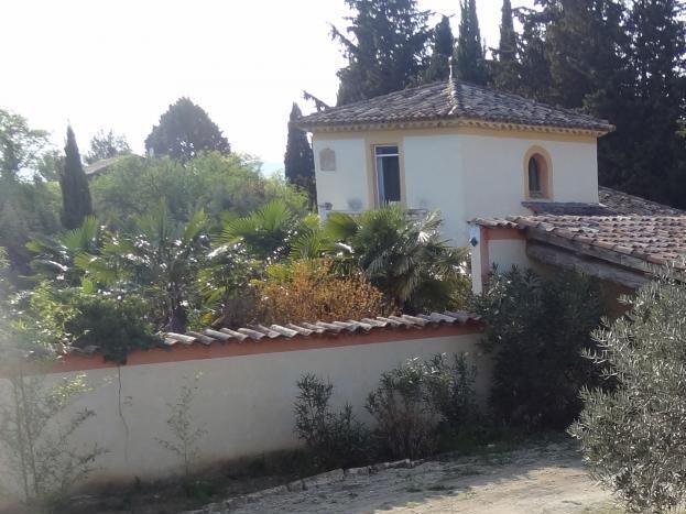 vue terrasse et terrain devant maison avec abri voiture derrière l'olivier