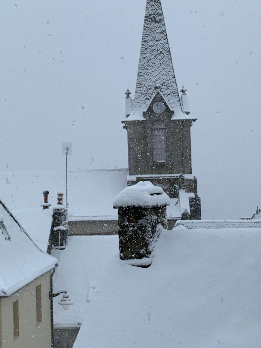 Vue de la chambre sur les toits enneigés du village