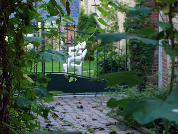 Entrée location et jardinet au fond de la ruelle depuis la rue