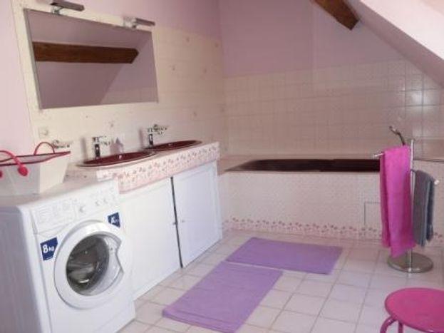 La salle de bain à l'étage avec baignoire, wc, lave linge