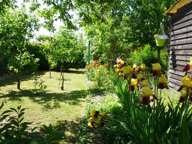 Une jardin fleuri et son local Accueil Vélos