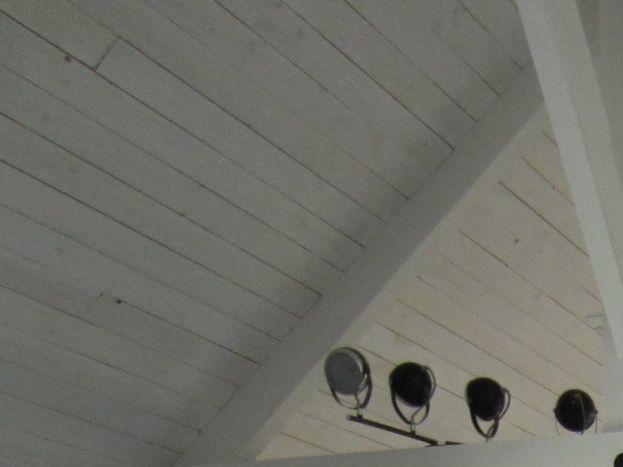 Salon vue de la salle d'eau (derrière le divan convertible, la chambre séparée par une palissade). Au fond de la pièce, se trouve l'entrée avec de grands placards et penderies.