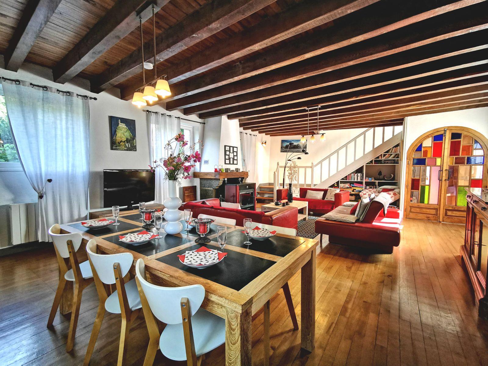 Pièce de vie avec table à manger et espace salon organisé autour d'une belle cheminée