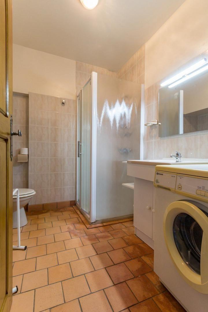 La salle d'eau incluant une vasque, une douche, un WC et la machine à  laver