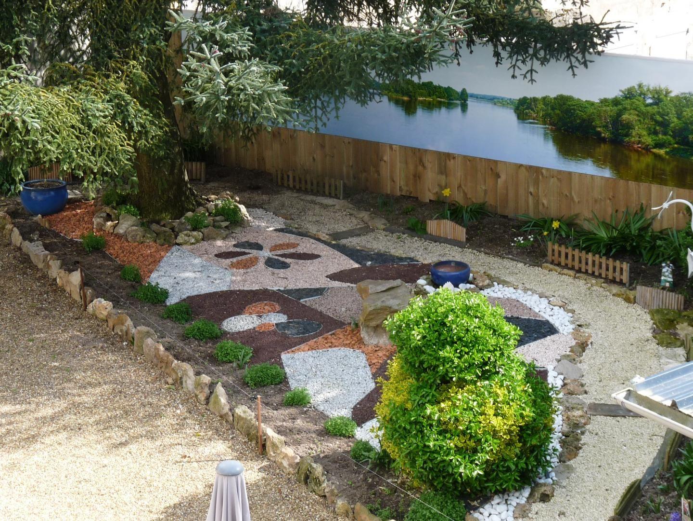 Jardin devant le gite : mosaïque (petits graviers) et fleuri l'été.