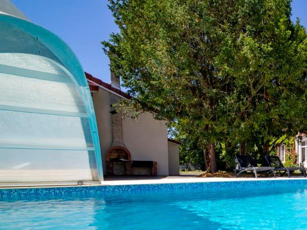 Une grande piscine extérieure munie d'un abri amovible aux beaux jours