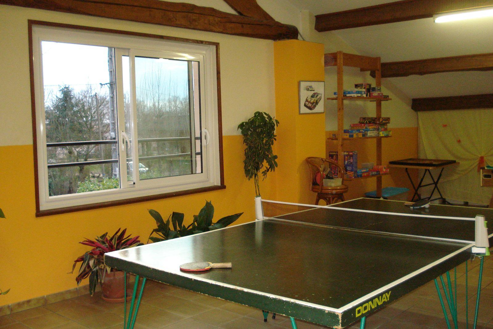Salle de jeux avec babyfoot, ping-pong, coin avec jouets et livres, bandes dessinées  pour enfants.