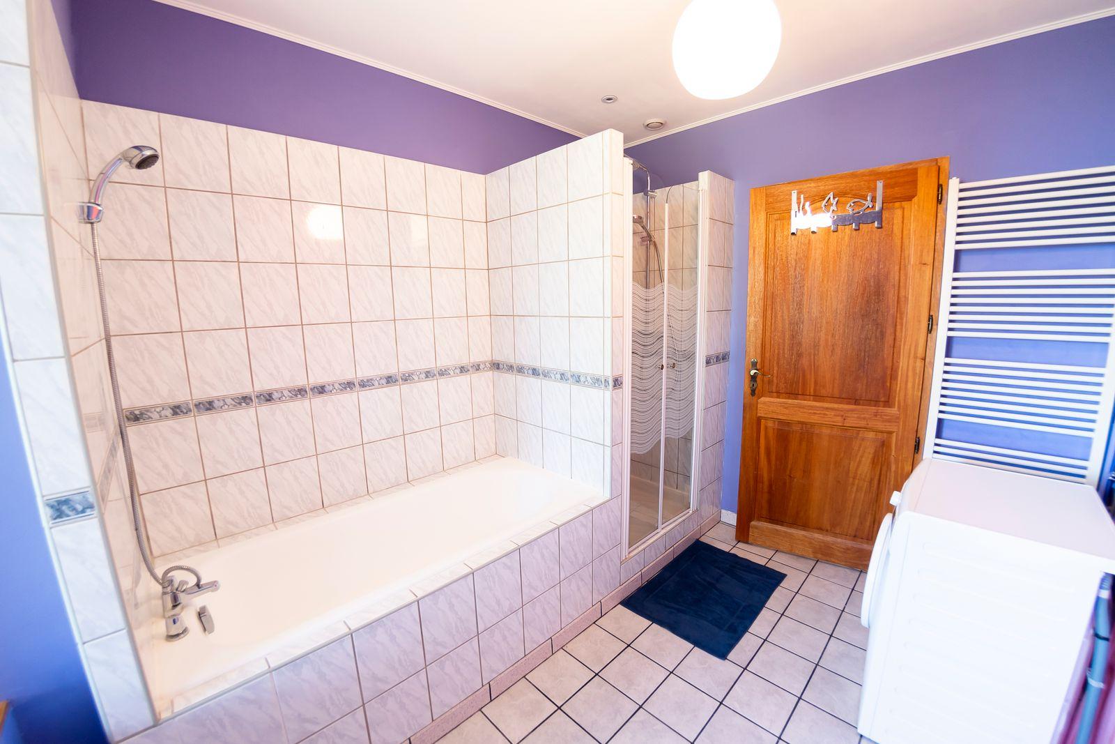 Salle de bains avec baignoire et douche